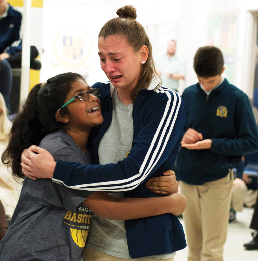 Photo by Benjamin Batchelor Eighth-grader Lily DeSpain hugs eighth-grader Swati Sajan, left, after winning the Haas Hall Academy Spelling Bee at the Fayetteville campus on Nov. 18, 2016. Using his fingers, eighth-grader Sam Bishop, who was runner-up, continues to spell out his final word on his hand.